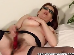 Mature redhead wearing nothing but her shades and stockings plays with her aged pussy